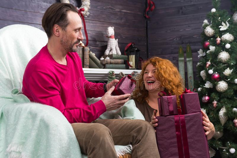 Happy woman holding beautiful presents and giving one to her husband. Surprised middle aged men feeling interested while looking at the lovely wrapped present stock image