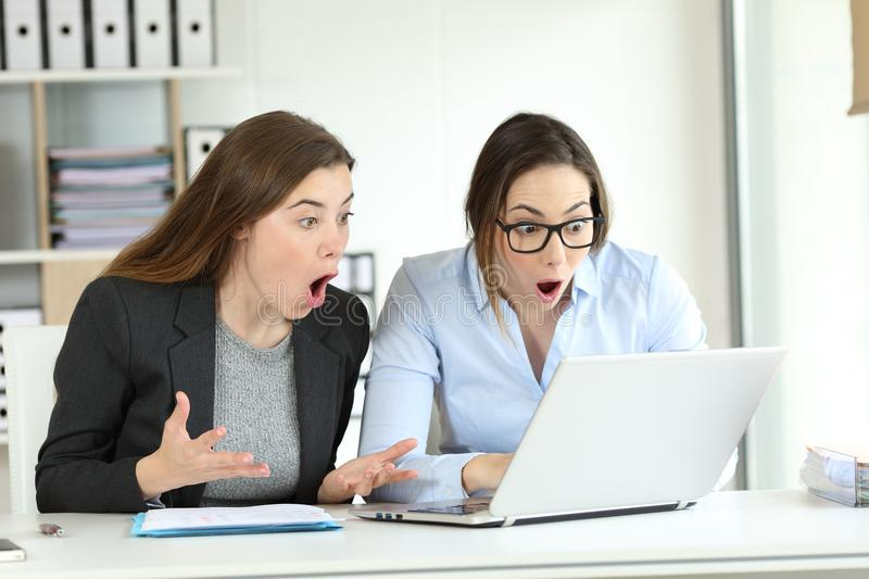 Surprised office workers reading online news. Surprised office workers reading together online news in a laptop royalty free stock photos