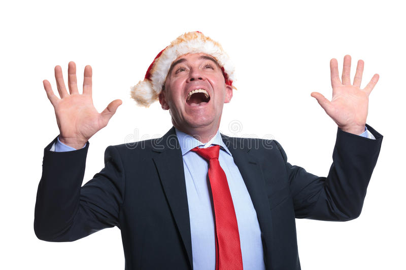 Surprised old business man wearing a santa claus hat is looking stock photo