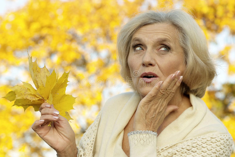 Surprised by the old woman. Standing on a yellow background royalty free stock image