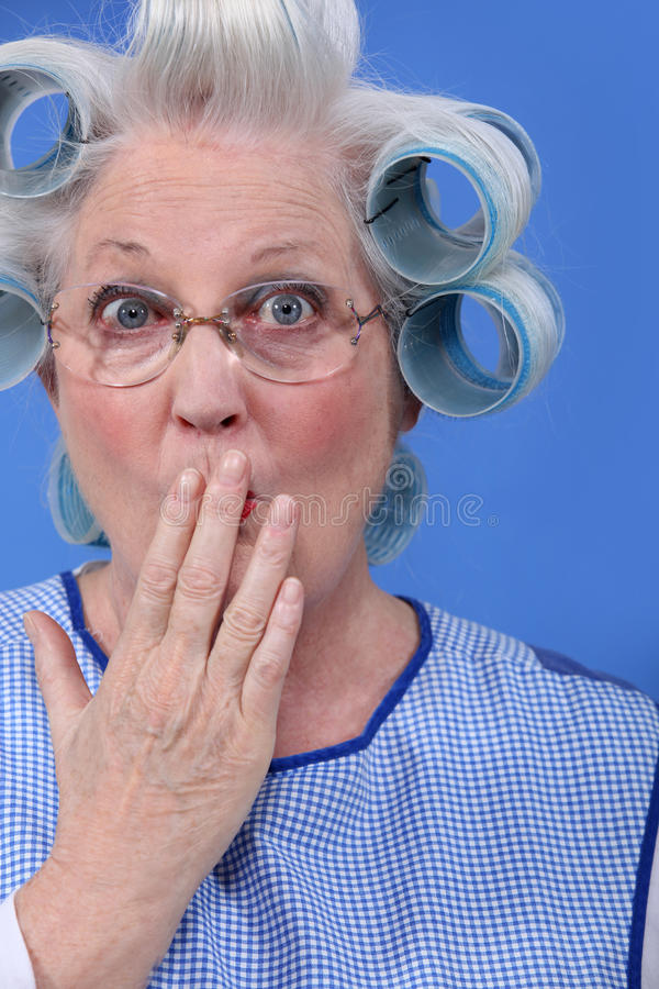 Surprised old woman. With her hair in rollers stock image