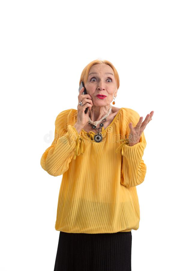 Surprised old woman with cellphone. Lady with eyes wide open. Hear and believe royalty free stock images