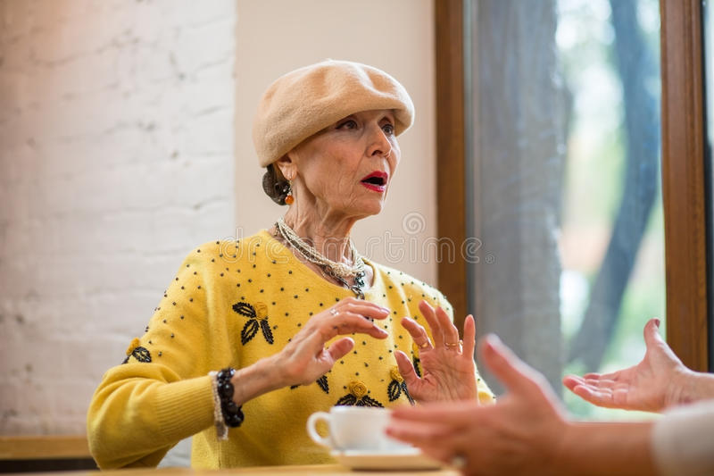 Surprised old woman. Lady at the cafe table. Truth be told royalty free stock images