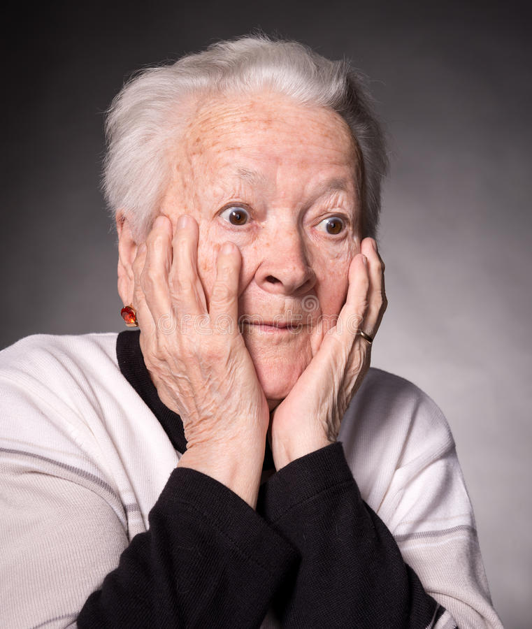 Surprised old woman. Portrait of surprised old woman on a gray background stock photo