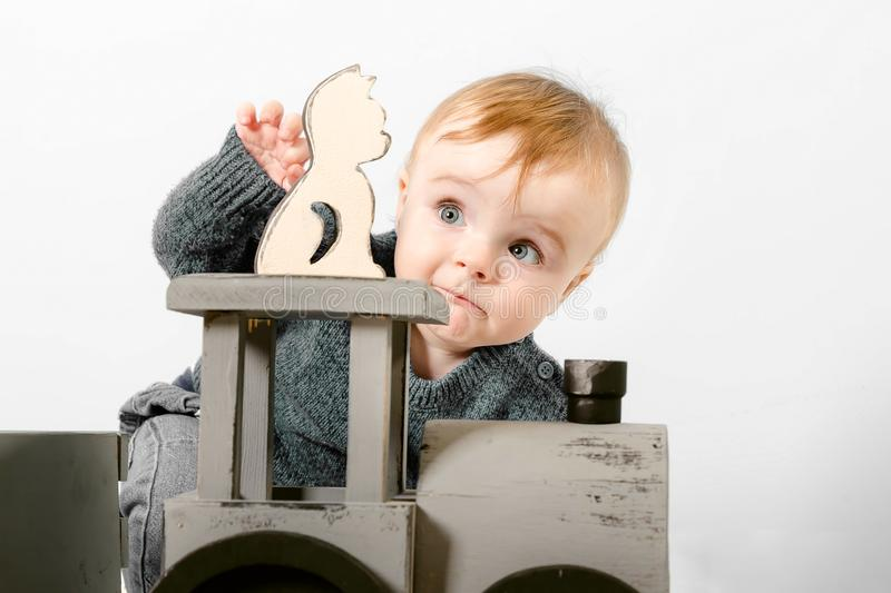 Surprised one year old child in a gray sweater plays wooden toys. Blonde baby boy on white background. Close up stock photo