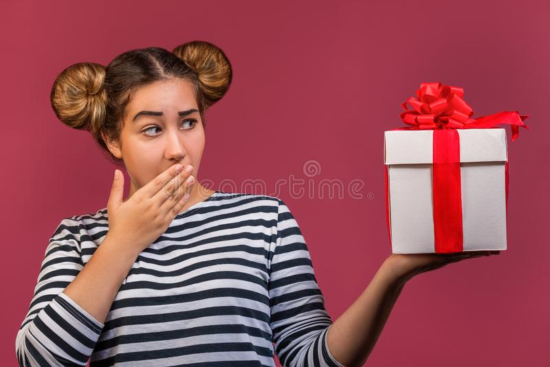Surprised portrait of hipster girl with funny hairstyle with gift box over pink background royalty free stock images