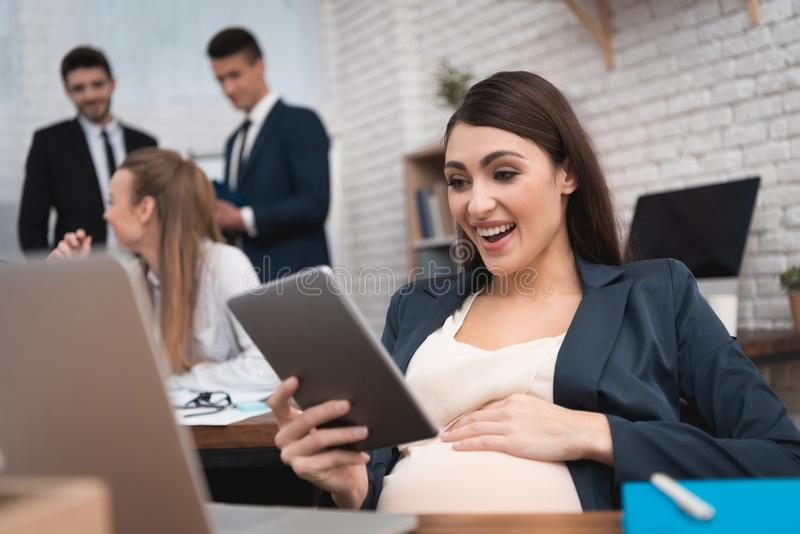 Surprised pregnant girl looks at tablet in office. Pregnancy at work. Pregnant woman at her desk. royalty free stock photos