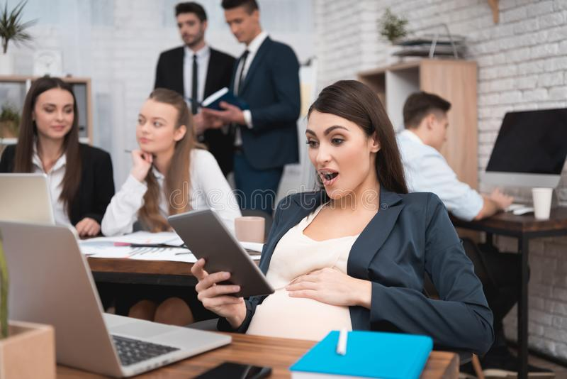 Surprised pregnant girl looks at tablet in office. Pregnancy at work. Pregnant woman at her desk. stock photography