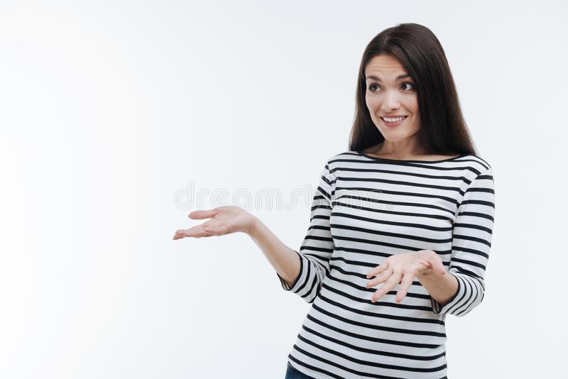Surprised pretty brunette looking sideways. What do you mean. Delighted female person wrinkling her forehead and keeping smile on her face while gesticulating royalty free stock photo