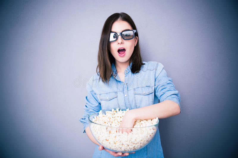 Surprised pretty woman in cinema glassses eating popcorn royalty free stock photography