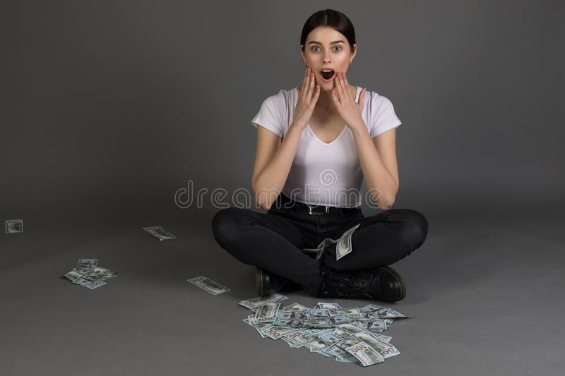 Surprised pretty young female with brunette hair , look with opened mouth at camera holding hands near face. Sitting in lotus position, money on the ground royalty free stock photos