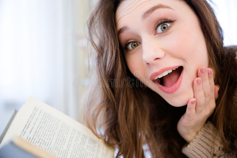 Surprised pretty young woman reading a book at home stock photo