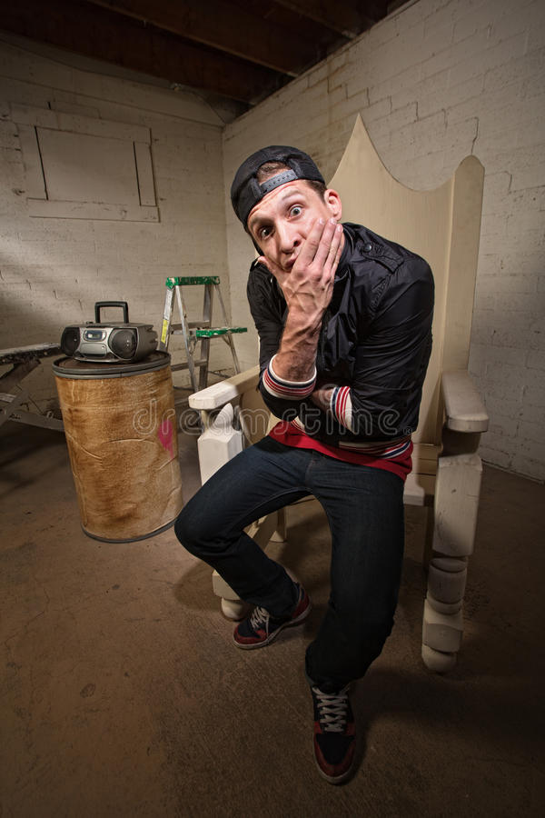 Surprised Rapper in Throne. Dumbfounded European rapper sitting on throne holding chin royalty free stock photography