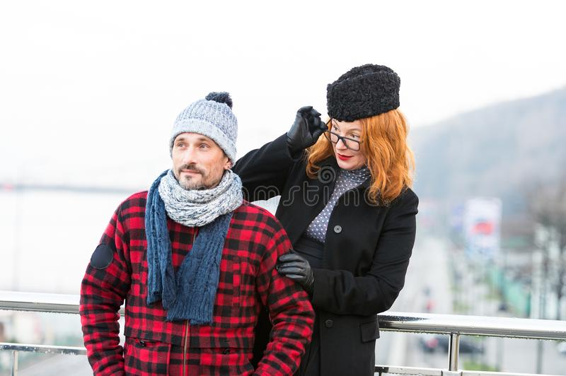Surprised red hair woman in glasses looked at stranger on bridge. Woman look over the glasses from the man back. stock photos