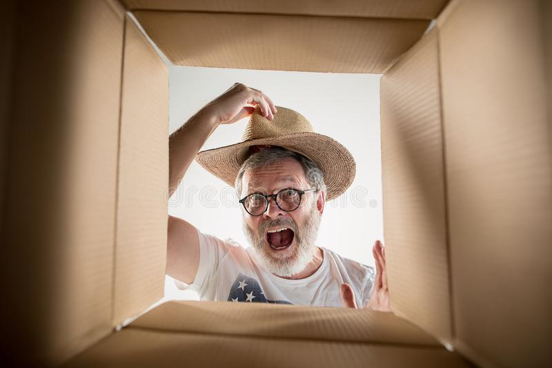 Man unpacking and opening carton box and looking inside. The surprised senior man unpacking, opening carton box and looking inside. The package, delivery royalty free stock images