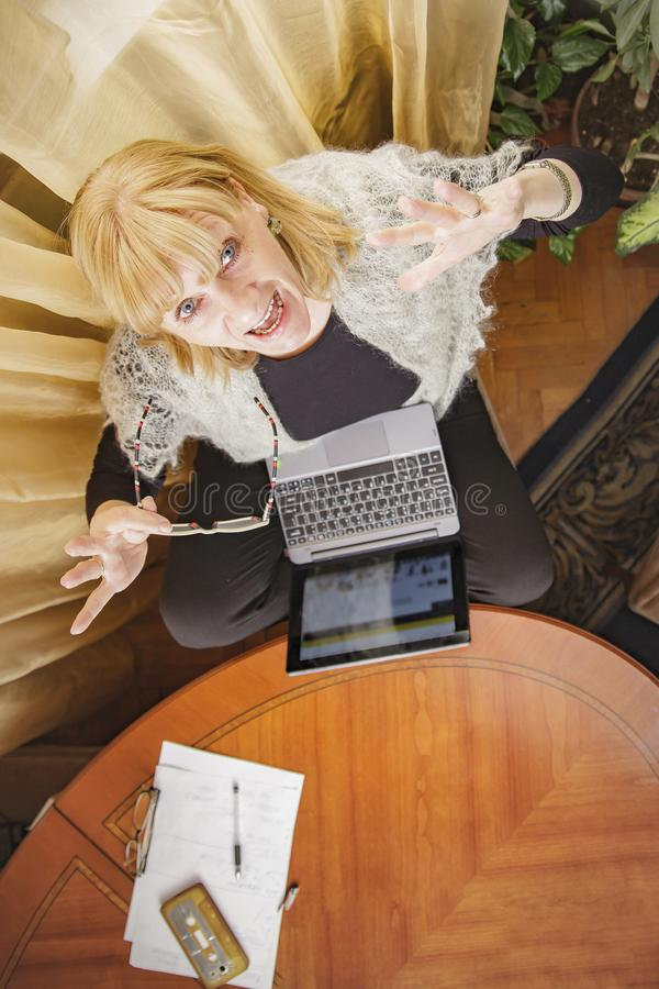 Surprise for an older lady. Surprised senior old woman sitting at her desk and using her laptop, above view royalty free stock photo