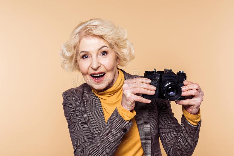 Surprised senior woman with film camera. Isolated on beige background royalty free stock images