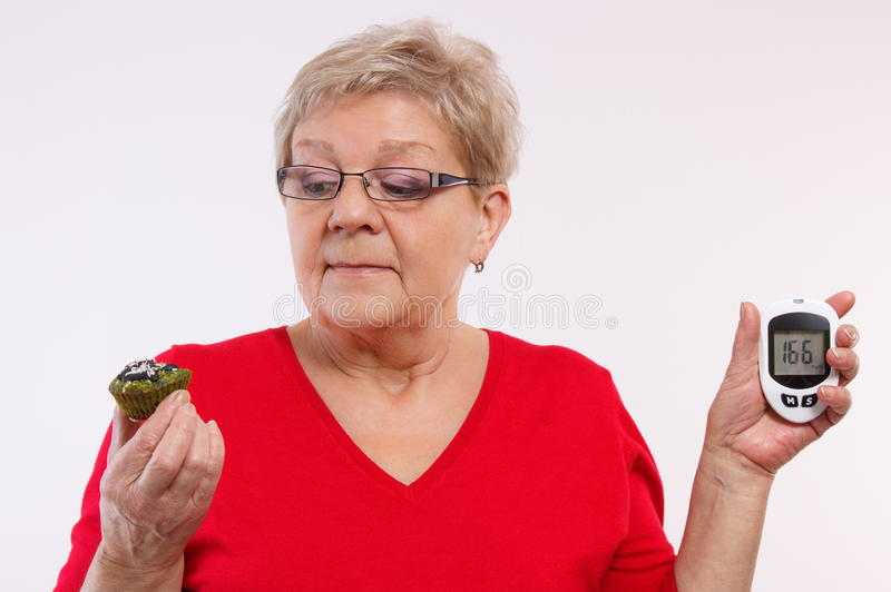 Surprised senior woman holding glucometer and fresh cupcake, measuring and checking sugar level, concept of diabetes. Surprised elderly woman holding glucose royalty free stock images