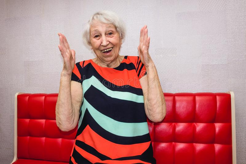 Surprised senior woman laughing out loud in living room. At home royalty free stock photos
