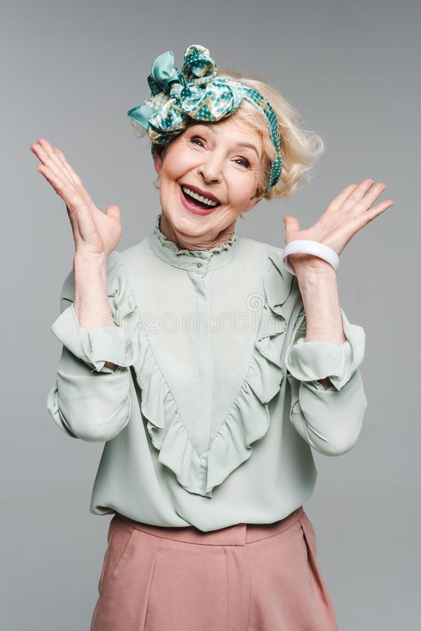 Surprised senior woman in stylish clothes. Isolated on grey royalty free stock images