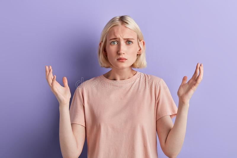 Surprised serious young woman expresses puzzled emotion stock photos