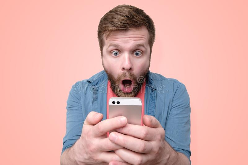 A surprised, shocked bearded man holds a smartphone in his hands and looks at the display with his mouth open and big eyes. stock photography