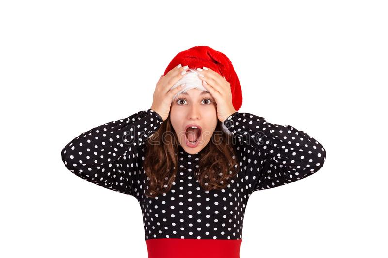 Surprised shocked beautiful woman in dress looking at the camera. emotional girl in santa claus christmas hat isolated on white ba stock images