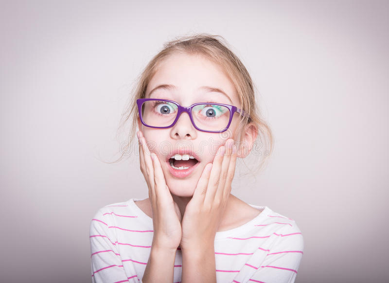 Surprised or shocked face of child girl in violet glasses royalty free stock images