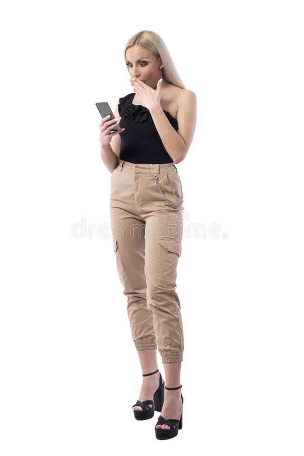 Surprised and shocked woman browsing discount on shopping smartphone app. Full body isolated on white background royalty free stock photography