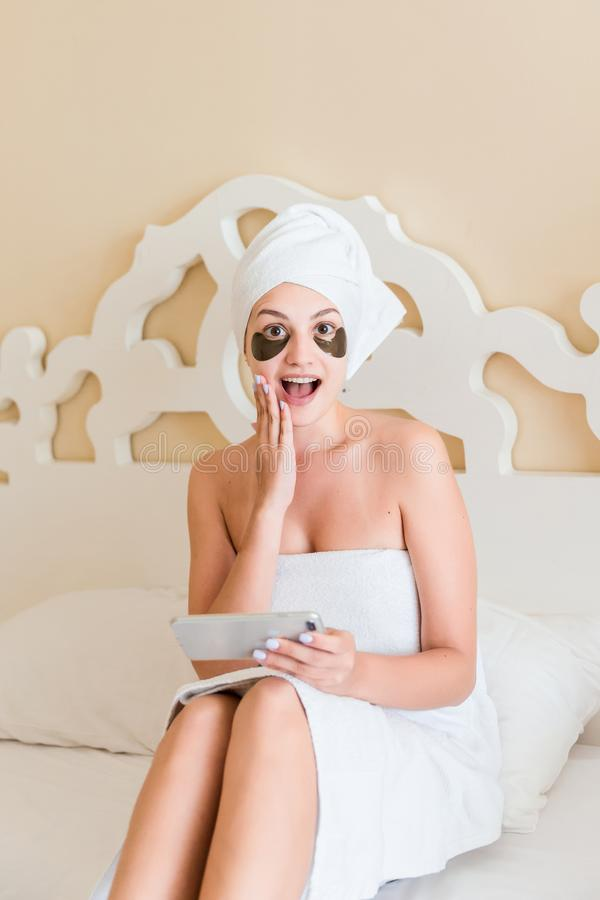 Surprised or shocked young woman with under eye patches got a bad news and using mobile phone in bathrobe lying in bed. Happy girl royalty free stock photography