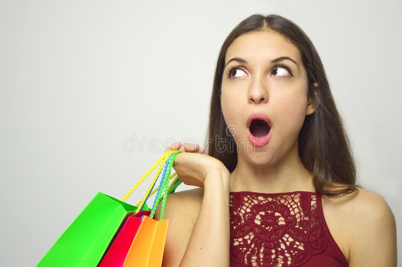 Surprised shopping woman looking to the side the copy space on white background stock photos