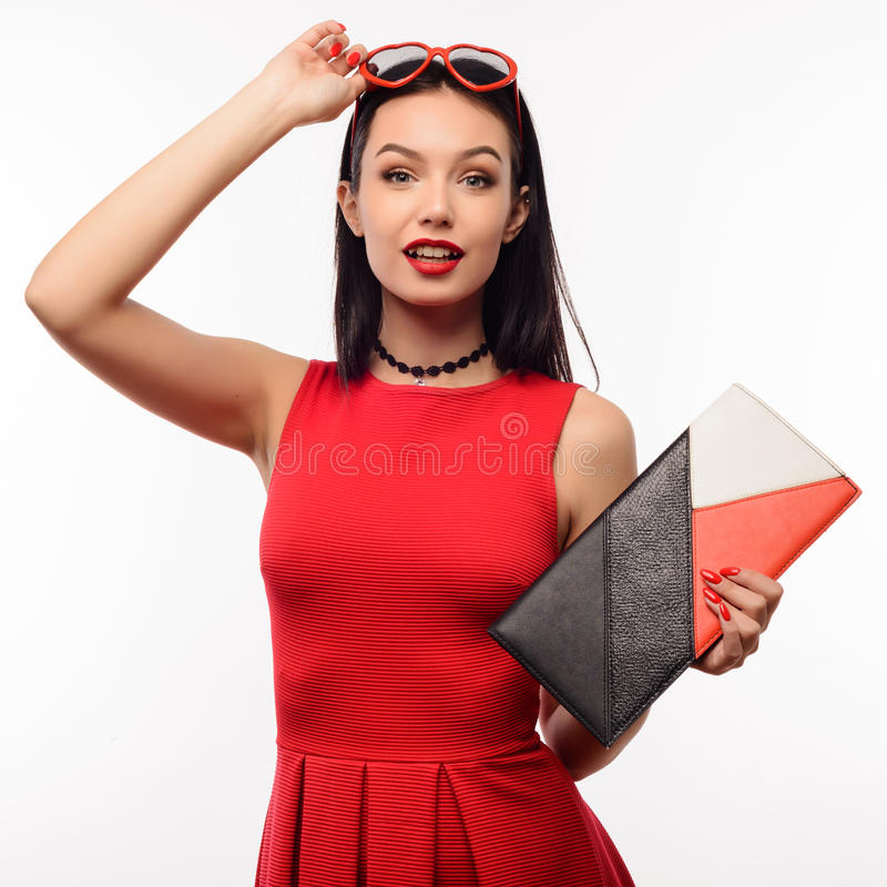 Surprised slender young woman in a red dress and clutch holds on to sunglasses in the shape of a heart stock photos