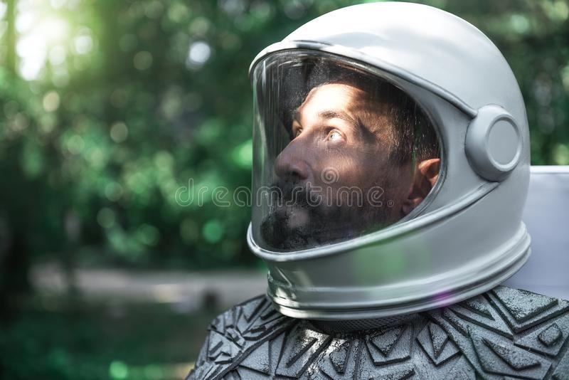 Astonished male cosmonaut glancing up. Surprised spaceman wearing helmet is looking at sunbeam with shock. Profile. Copy space on left side stock image