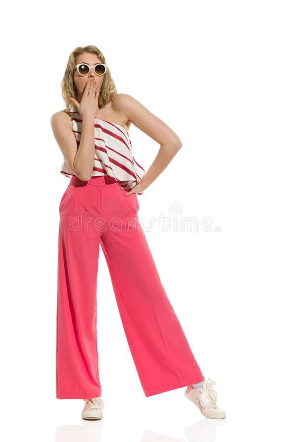 Surprised Stylish Young Woman In Red Wide Leg Trousers And Sunglasses Is Holding Hand On Mouth. Surprised young woman in red wide leg trousers and sunglasses is royalty free stock photo