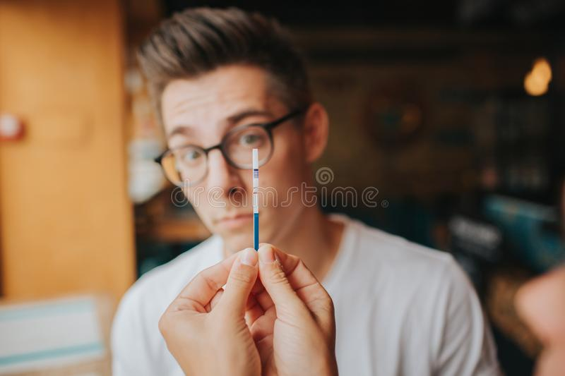 Surprised Teenage couple holding pregnancy test. Woman Show Man Positive Pregnancy Test Conflict Relationships Problem stock image