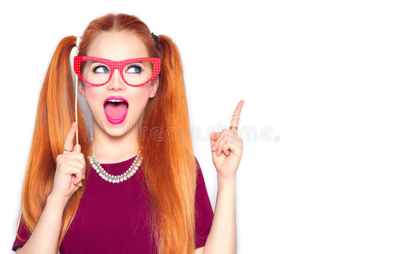 Surprised teenage girl holding funny paper glasses on stick royalty free stock image