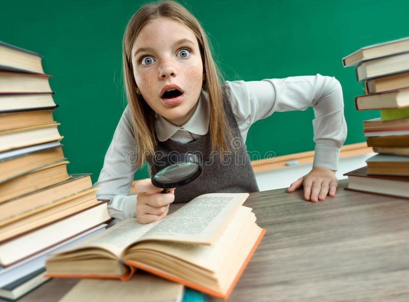 Surprised teenage girl with magnifying glass surrounded by piles of books stock image