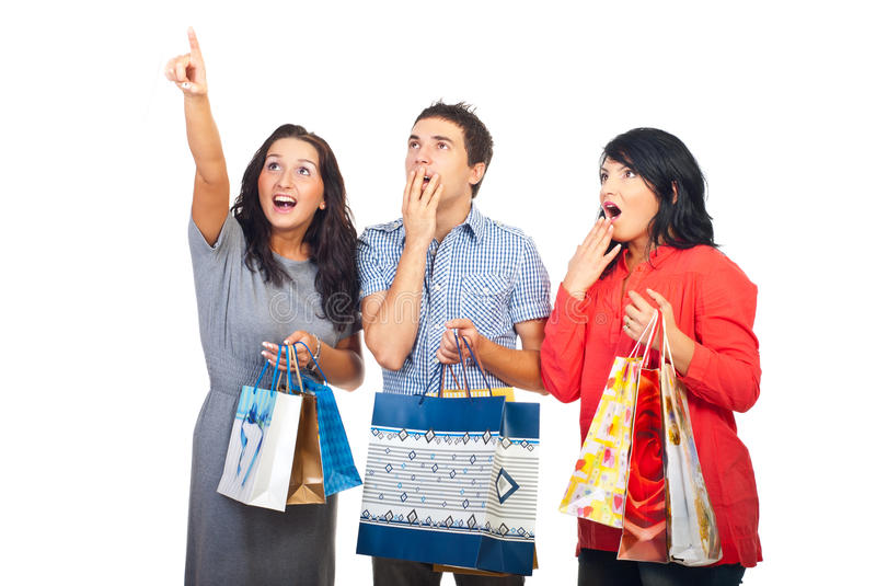 Surprised three friends at shopping looking up stock image