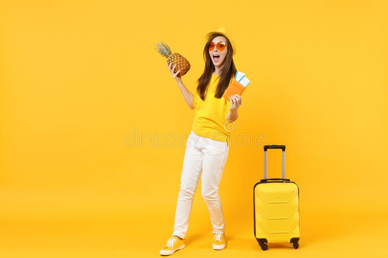Surprised traveler tourist woman in hat holding passport tickets fresh pineapple fruit isolated on yellow orange. Background. Passenger traveling abroad on royalty free stock photo