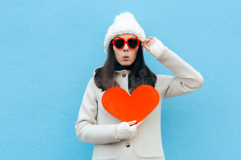 Funny Woman in Love Holding a Heart on Blue Background. Surprised Valentine Girl having a sudden crush royalty free stock photo