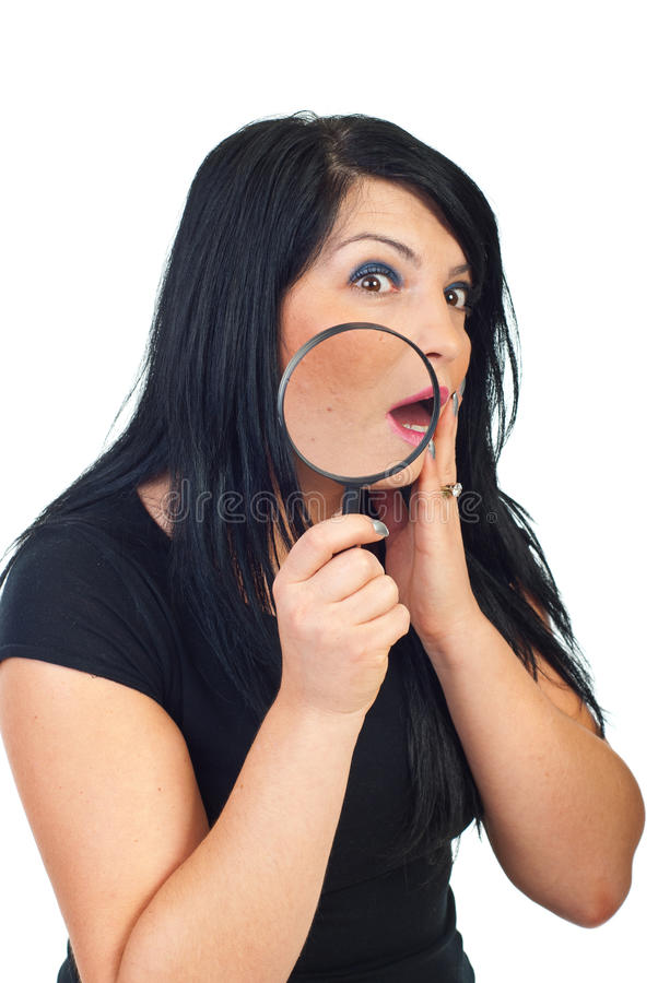 Surprised woman with acne. Scared woman with acne holding a magnifying glass and checking her face in the mirror isolated on white background royalty free stock photo