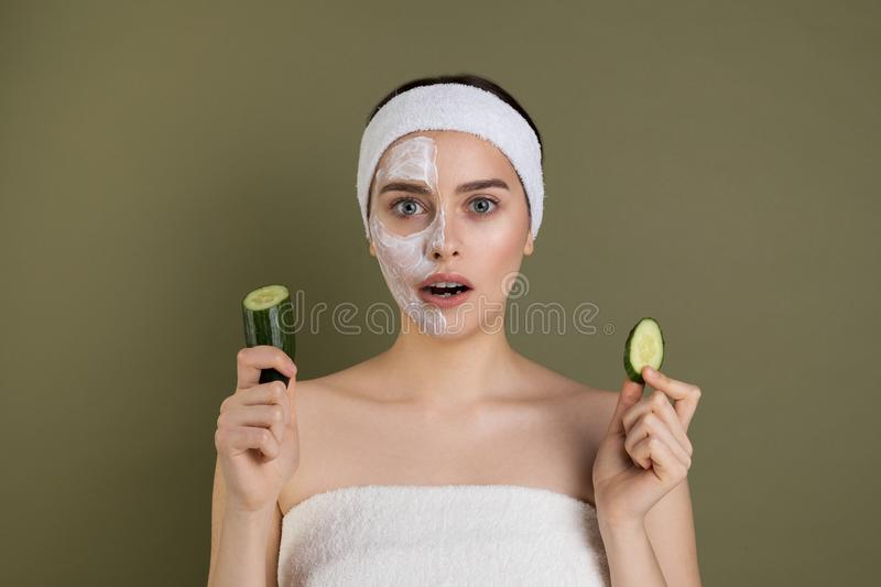 Surprised woman with bare shoulders loking at camera with open mouth, white mask on half of her face. Holding cucumber in hands  on green background stock photography