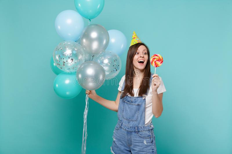 Surprised woman in birthday hat keeping mouth open, hold round lollipop, celebrating with colorful air balloons isolated. On blue turquoise background. Birthday royalty free stock photography