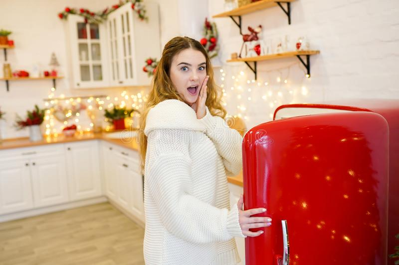 Surprised woman in christmas decorated kitchen, new year holiday stock photo