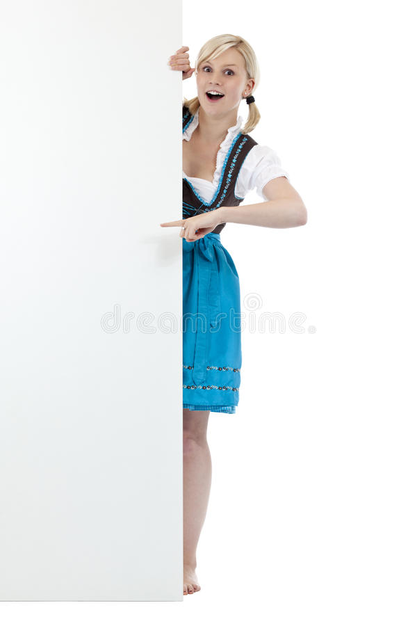 Surprised woman in dirndl pointing at blank sign royalty free stock photography