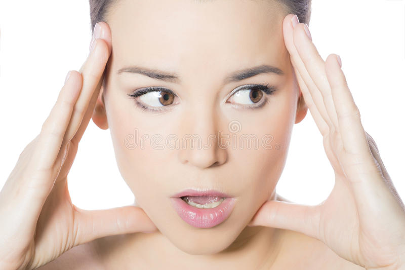 Surprised woman. Face of a surprised woman holding her head stock images