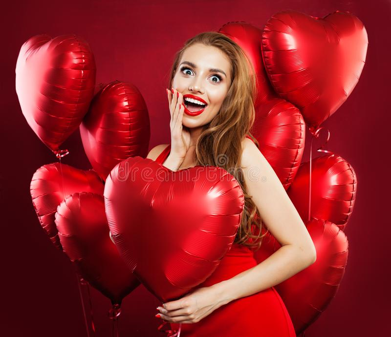 Surprised woman holding balloons red heart, portrait. Girl with red lips makeup wearing red dress. Gift, sale and Valentine`s day royalty free stock photos