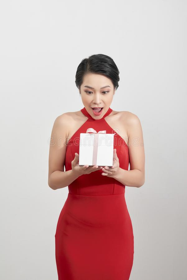 Surprised woman holding gift over white background royalty free stock photography