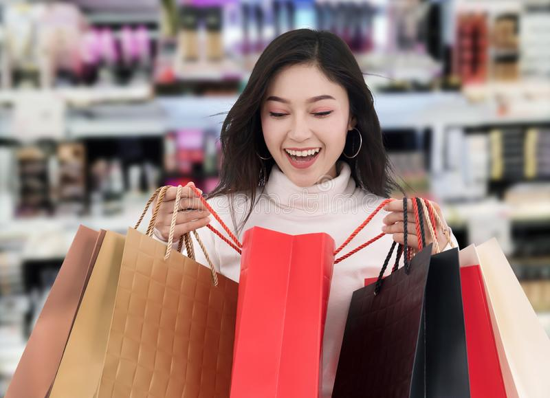 Surprised woman holding opened shopping bag at mall stock photography