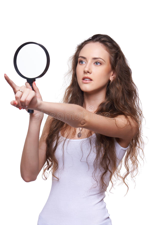 Surprised woman looking through magnifying glass stock image